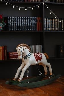 Cheval jouet pour enfants debout à côté d'une bibliothèque