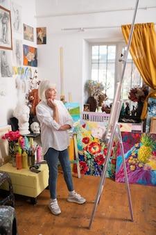 Chevalet à dessin proche. femme d'âge moderne portant des jeans et des baskets debout près de chevalet de dessin