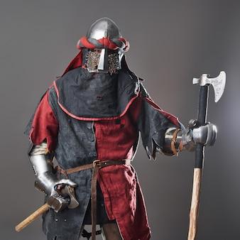 Chevalier médiéval sur fond gris. portrait de guerrier visage brutal avec armure de cotte de mailles vêtements rouges et noirs et hache de combat.
