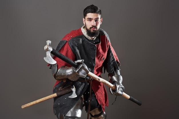 Chevalier médiéval sur gris. portrait de guerrier visage sale brutal avec des vêtements rouge et noir d'armure cotte de mailles et une hache