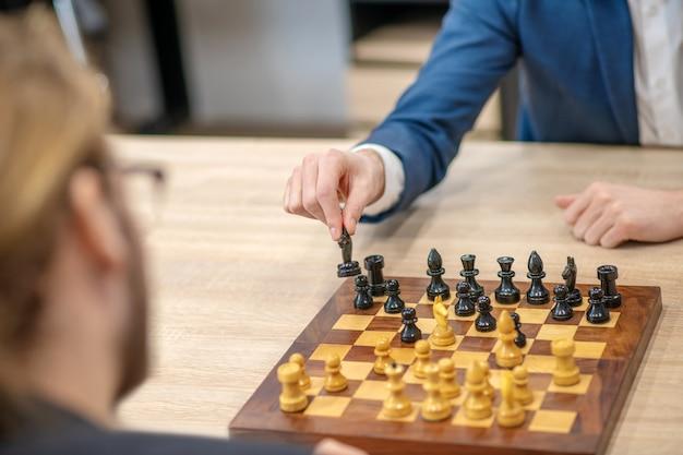 Les chevaliers bougent. mâle main tenant et réorganiser le chevalier noir sur l'échiquier pendant le jeu à l'intérieur