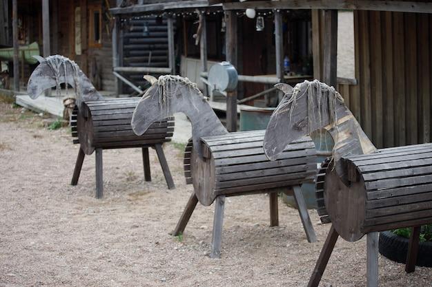 Des chevaux de bois se tiennent dans la cour du village. photo de haute qualité