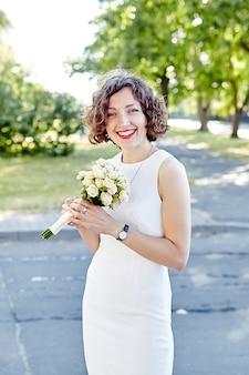Cheveux bouclés jeune femme en robe blanche en plein air