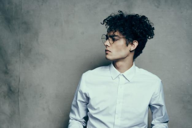 Cheveux bouclés jeune homme en chemise costume classique modèle de studio de photographie sur fond de tissu