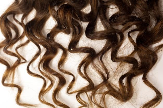 Cheveux bruns bouclés, isolés sur blanc
