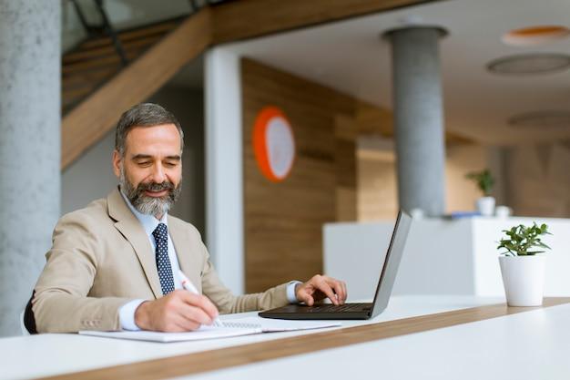 Cheveux gris homme d'affaires senior travaillant sur ordinateur portable au bureau moderne