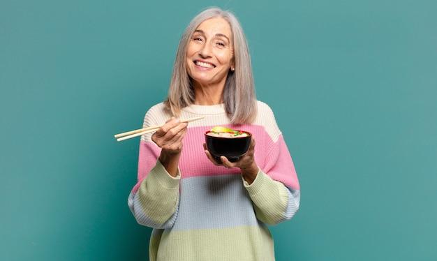 Cheveux gris jolie femme avec un bol de ramen