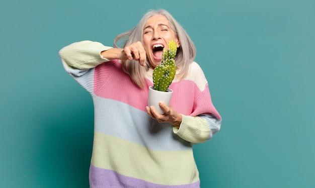 Cheveux gris jolie femme avec un cactus