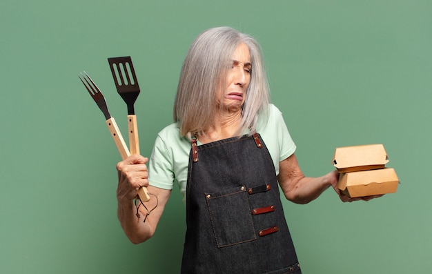 Cheveux gris jolie femme chef barbecue