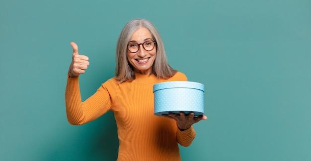 Cheveux gris jolie femme avec un coffret cadeau