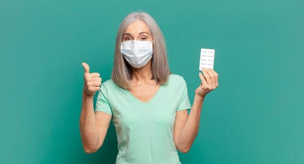 Cheveux gris jolie femme avec un masque protecteur et des pilules