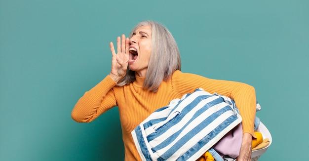 Cheveux gris jolie femme de ménage laver les vêtements