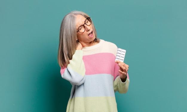 Cheveux gris jolie femme avec des pilules de maladie