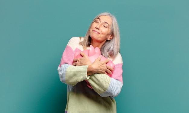 Cheveux gris jolie femme avec une tirelire