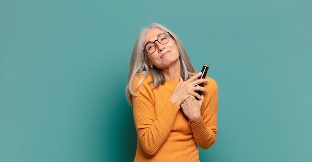 Cheveux gris prewoman prenant une bière