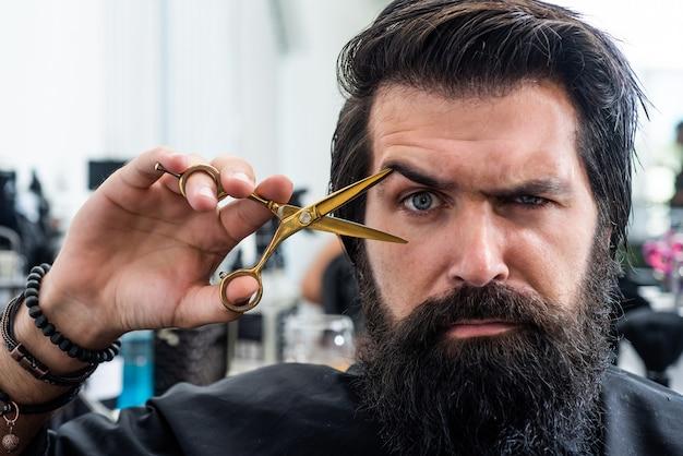 Des cheveux juste fabuleux. maître barbier coupe les cheveux avec des ciseaux. hipster mature avec barbe chez le coiffeur. hipster brutal avec moustache fait une nouvelle coiffure. salon de coiffure. coiffure à la mode masculine. coupe de cheveux parfaite.