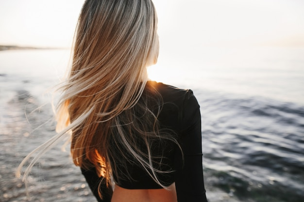Les cheveux longs de la jeune fille se bouchent sur la mer