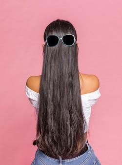 Cheveux longs avec des lunettes de soleil par derrière