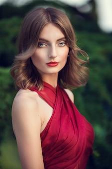 Cheveux à la mode tresse échevelée autour de la tête. heureuse belle jeune fille modèle dans le parc de fleurs d'été.