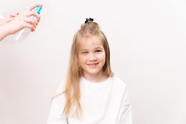 Sur les cheveux d'une petite fille a pulvérisé un moyen pour un peignage facile sur un fond blanc. cosmétiques pour le soin des cheveux des enfants.