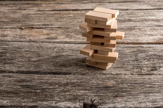 Chevilles en bois placées dans une tour en forme de structure. conceptuel de la stratégie commerciale, de l'éducation et du jeu de loisirs.