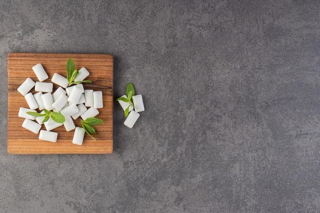 Chewing-gums blancs placés sur une table en pierre.