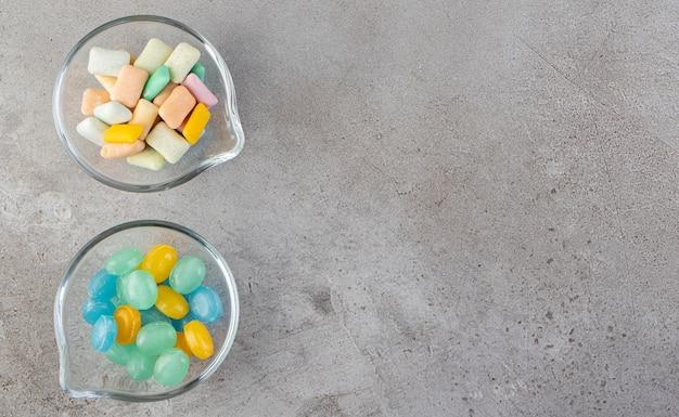Chewing-gums colorés dans des bols placés sur une table en pierre.