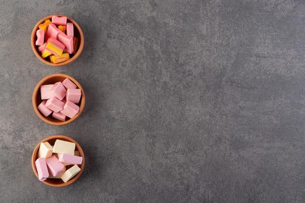 Chewing-gums colorés placés dans des bols en argile sur une table en pierre.