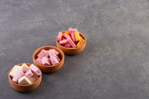 Chewing-gums colorés placés sur une table en pierre.