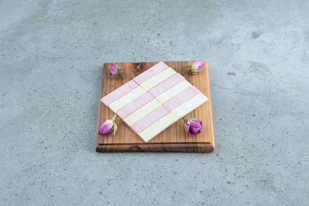 Chewing-gums colorés avec des roses séchées sur planche de bois.