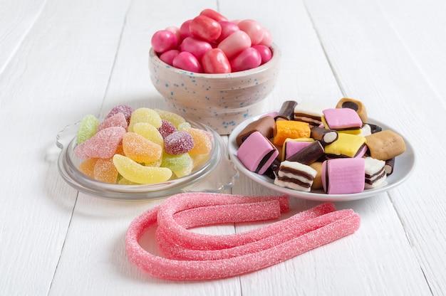 Chewy gummies bonbons à la réglisse gomme aux fruits dans des bols concept de vacances bébé traite des aliments malsains