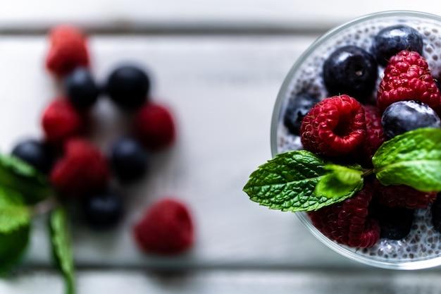 Chia aux baies sauvages. framboises et myrtilles. dessert délicieux et sain sur une table rustique en bois blanc. point de vue zenith