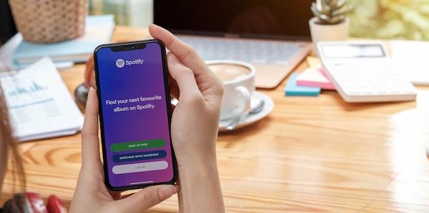 Chiang mai, thalande - 27 juillet 2021 : personne tenant un tout nouvel apple iphone xs avec le logo spotify à l'écran. spotify est un service de streaming musical populaire.