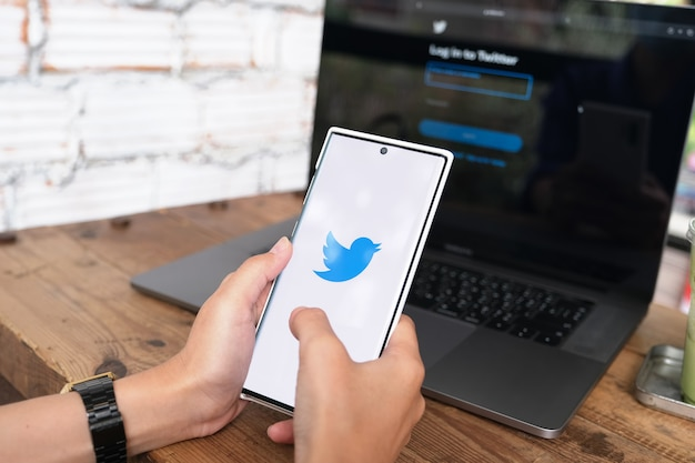Chiangmai, thalande - 6 juin 2021 : femme tenant un smartphone mobile avec le logo twitter à l'écran. twitter est un service en ligne de médias sociaux pour le microblogging et la communication en réseau.