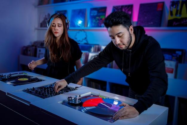 Chica y chico dj mezclando msica en una tienda de discos de vinilo usando un tornamesa retro