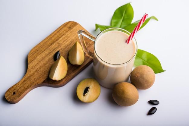 Chickoo, chikoo ou sapota milkshake savoureux et sain. c'est un fruit sain mélangé avec du lait et de la glace servi dans un verre sur fond coloré ou en bois. mise au point sélective