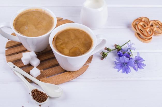 Chicorée de plantes médicinales, régime alimentaire chicorée dans une tasse de lait pour le petit déjeuner sur un tableau blanc.