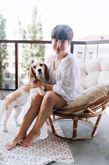 Chien beagle debout sur deux pattes posant à côté de jolie fille brune avec pédicure blanche se détendre sur la terrasse