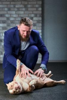 Chien bulli et son propriétaire, son maître aimant qui tient le chien dans ses bras, l'embrasse et l'embrasse. le chien se sent bien dans les mains du propriétaire