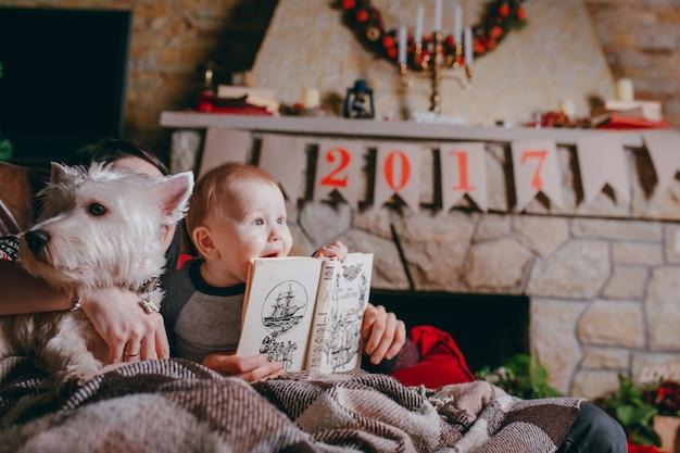 Chien à côté de bébé ayant un livre dans les mains