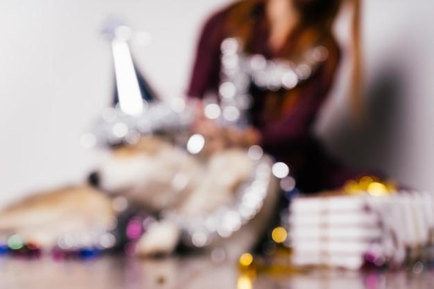 Un chien dans un chapeau de fête est assis sur un fond de cadeau, flou