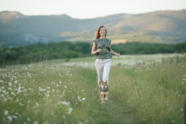 Un chien et une femme qui traverse un champ d'herbe verte