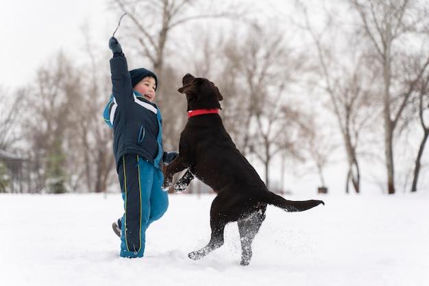 Chien jouant avec un enfant dans la neige en famille