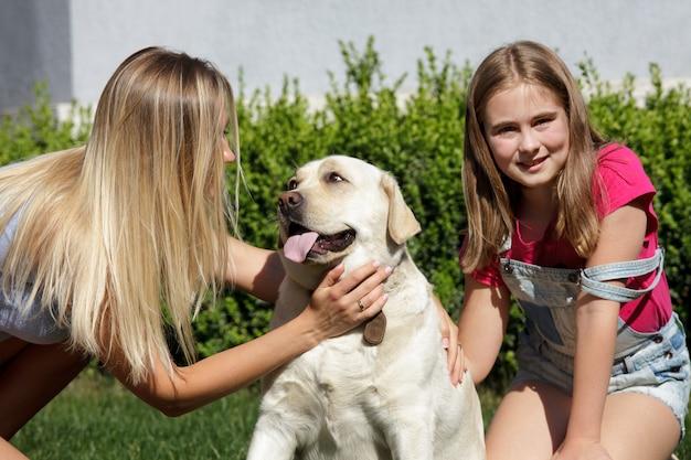 Chien labrador, mère et fille sur l'herbe verte près de la maison