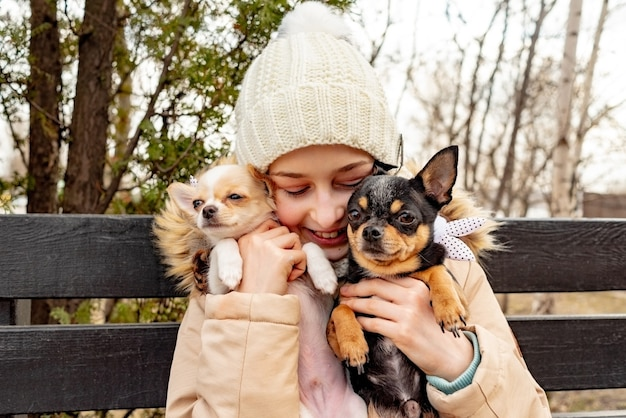 Chienne. adolescente avec deux chiens chihuahua dans ses bras. chiens en vêtements. chiot propriétaire ami.