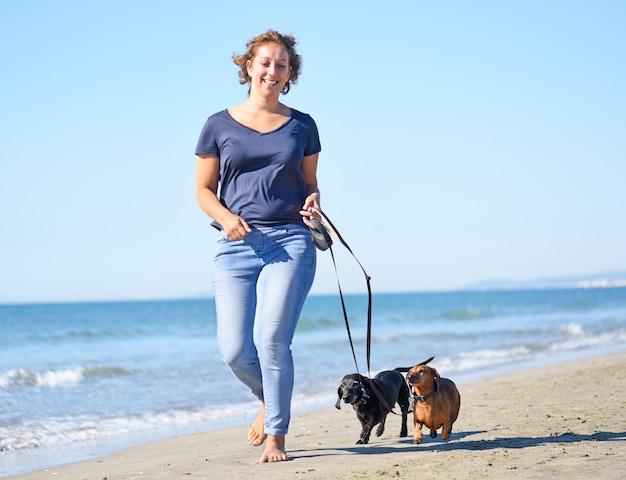 Chiens et femme sur la plage