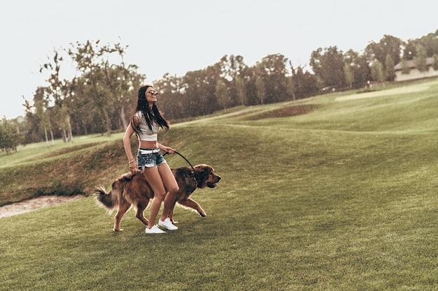 Les chiens rendent la vie meilleure. toute la longueur de la belle jeune femme jouant avec son chien et souriant en courant à l'extérieur