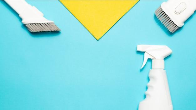 Chiffon en microfibre, accessoires pour aspirateur et spray nettoyant sur fond bleu, vue de dessus, espace de copie. les fournitures de nettoyage.