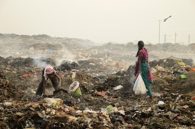Les chiffonniers recherchent des matières recyclables dans les poubelles et la pollution de l'air en inde