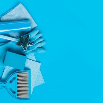Des chiffons, des gants en caoutchouc, des éponges, une brosse et une pelle avec un balai.